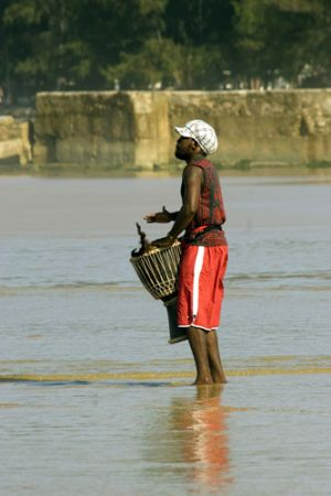 A local youth drumming on the beach at Tofo,