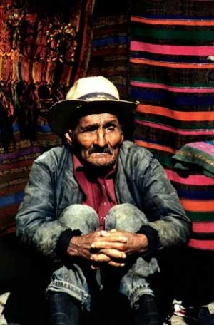 Old Man Beside a Pile of Colourful Blankets